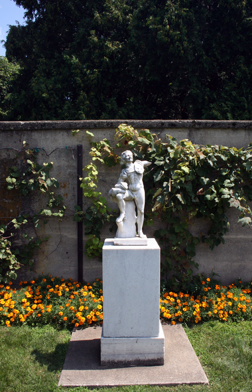 Marble Faun against stone wall with flowers