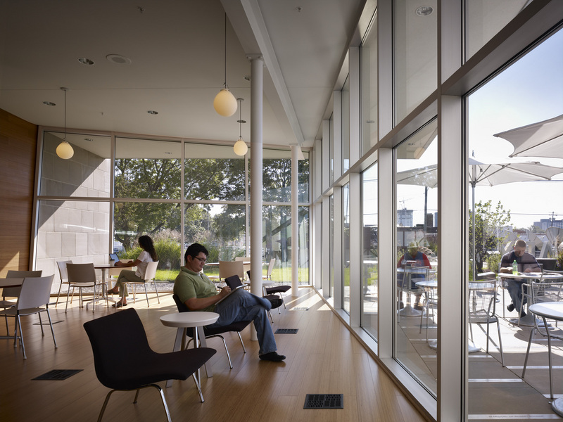 Cafe seating area inside the library, with a view of the outdoor patio